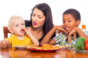 Jonge moeder met kinderen die pizza eten, geïsoleerd op een witte achtergrond